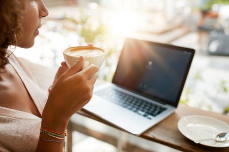 filiżanka kawy: Kadrowania obrazu kobieta picia kawy z laptopem na stole w restauracji. Młoda dziewczyna trzyma filiżankę kawy w kawiarni.