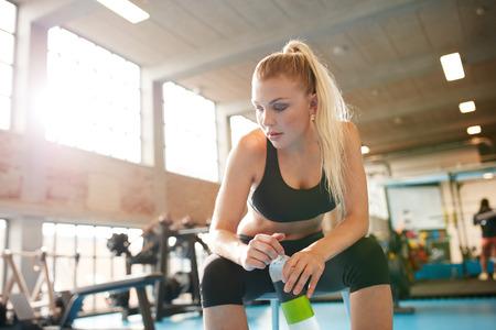 personas tomando agua: Retrato de mujer joven de descanso despu�s de hacer ejercicio en el gimnasio. Fitness femenino tomando descanso despu�s de la formaci�n de la sesi�n en el club de salud. Mujer sosteniendo una botella de agua sentado en un taburete y mirando hacia abajo. Foto de archivo