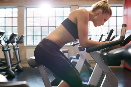 self conscious: Fitness woman on gym bicycle resting after workout. Caucasian young female athlete doing fitness training on a stationary bike in health club.