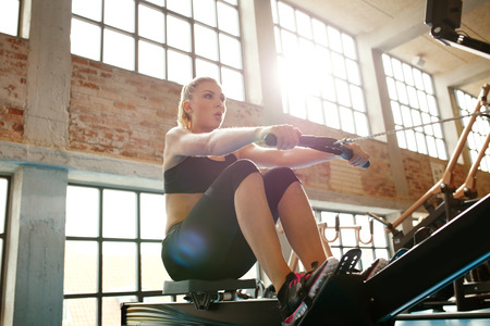 machines: Young caucasian woman doing exercises on fitness machine in gym. Female using rowing machine at  fitness club. Stock Photo