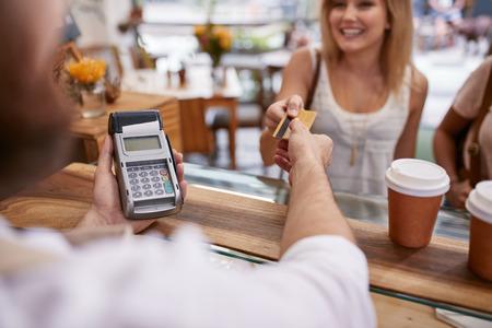 pagando: Cliente pagar su pedido con tarjeta de crédito en un café. Camarero que sostiene una máquina de lector de tarjetas de crédito y devolver la tarjeta de débito para el cliente femenino después de los pagos. Foto de archivo