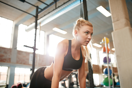 self conscious: Indoor shot of young fitness woman doing push ups in gym. Caucasian female working out in health club.