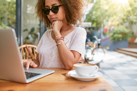 hair curly: Tiro al aire libre de la joven mujer africana en el café de la acera leer mensajes en su ordenador portátil. Chica joven con estilo que se sienta en la cafetería navegar por internet en su ordenador portátil.