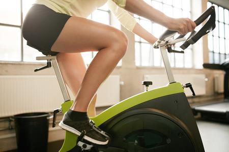 motion: Beskurna skott av fitness kvinna som arbetar på motionscykel på gymmet. Kvinna utövar på cykel i hälsoklubb, fokus på ben.