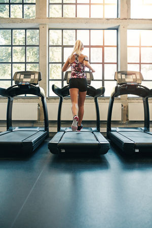 self conscious: Rear view of young female running on treadmill in gym. Fitness woman jogging indoors in health club