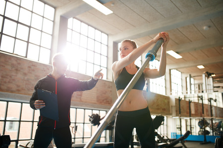 Mujer de la aptitud que ejercita con el preparador físico en el gimnasio. Mujer que se resuelve con su entrenador personal en el club de salud. Foto de archivo - 48840529