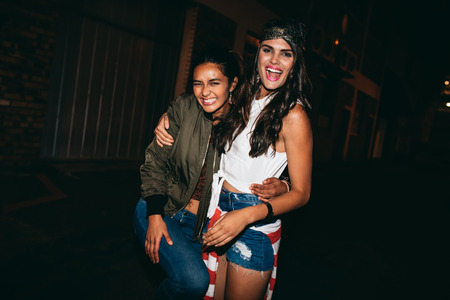 people laughing: Portrait of two young female friends having fun outdoors. Women enjoying in outdoor party in evening.