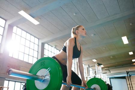 重い重みを持つトレーニング フィットネス若い女性と判断。白人女性アスリート重量挙げのジムでエクササイズを行います。