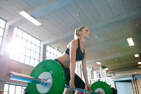 Determined young fitness woman training with heavy weights. Caucasian female athlete doing weight lifting workout in gym. Stock Photo