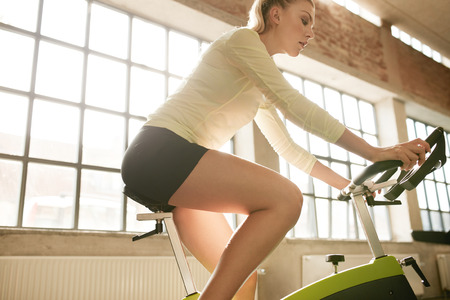 health and fitness: Side view of fitness woman on bicycle in gym. Young female athlete spinning on bicycles at health club.