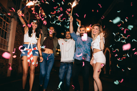 celebration: Grupa młodych ludzi urządza przyjęcie, na zewnątrz. Wielorasowe młodzi mężczyźni i kobiety doceniają z konfetti. Najlepszy przyjaciel o imprezę w nocy.