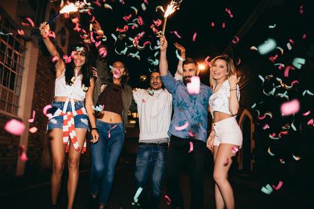 oslava: Skupina mladých lidí večírek, venku. Mnohonárodnostní mladých mužů a žen slaví s konfetami. Nejlepší přítel s párty v noci. Reklamní fotografie