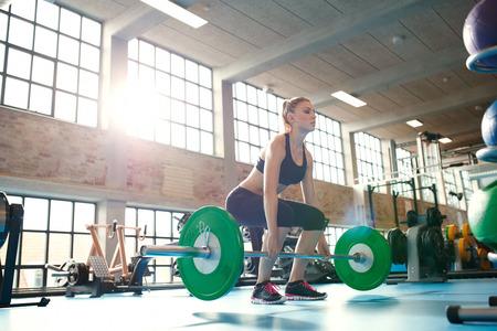 levantando pesas: Mujer joven que trabaja duro en el gimnasio. Fit pesos de elevaci�n de la mujer atleta en club de salud.