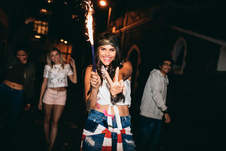 new look: Portrait of cheerful young woman holding a sparkler and showing victory sign. Young people celebrating 4th of july at night outdoors.