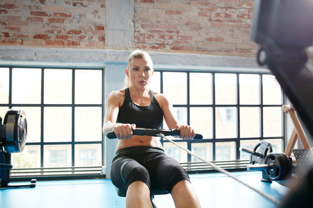 Caucasian female using rowing machine in the gym. Young woman doing cardio workout in fitness club. Stock Photo
