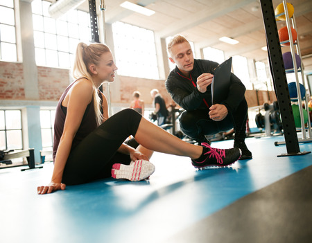 Personal trainer helping young woman on her work out routines in gym. Female sitting on floor with her personal trainer showing fitness report on a clipboard.