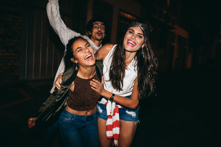 Portrait of three young friends having party outdoors. Cheerful young best friends hanging out at night. Фото со стока