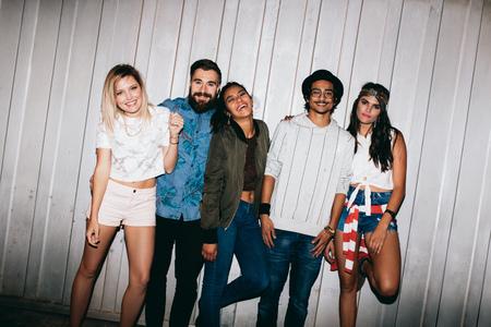 personas festejando: Retrato de jóvenes amigos alegre de pie junto al aire libre. Los jóvenes multirraciales salir por la noche. Foto de archivo