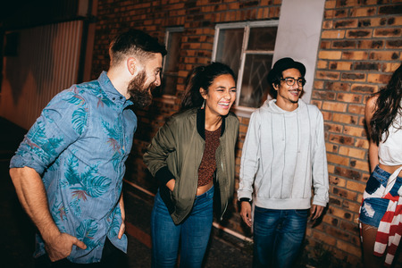 evening out: Multi-ethnic group of friends chatting and laughing at the party. Young men and women hanging out together at rooftop party. Stock Photo