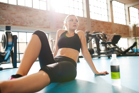 water sport: Portrait of a young woman during a break in the gym. Caucasian female sitting on floor looking away, resting after workout.