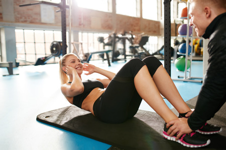 fit body: Shot of an young woman doing sit-ups while a young man steadies her feet. Female doing abs crunches with the help of her personal trainer at health club.