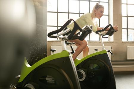 ジムでのエアロバイクの働く女性に合います。回転自転車フィットネス センターでのトレーニングをしている陽気な女性の屋内撮影。