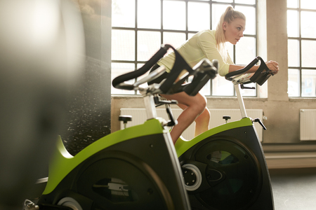 Fit woman working out on exercise bike at the gym. Indoor shot of a sportive woman doing fitness training on spinning bicycle at health club.