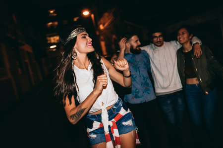 Portrait of pretty young woman dancing with her friends in background. Happy young female enjoying in a party with friends. Stock Photo
