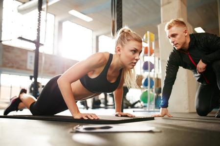 utbildning: Fitness kvinna träna med tränare i gymmet. Kvinna gör armhävningar träna med sin personliga tränare vid hälsoklubb.