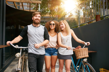 Three young people walking down the street with their bicycles and having fun. Male and female friends with their bike on city street.