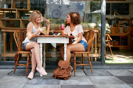 women coffee: Young friends sitting at coffee shop drinking mocktails. Young women meeting at sidewalk table having refreshing drinks.