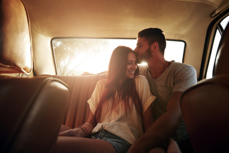 romance: Portrait de détente jeune couple sur un road trip assis dans le siège arrière de la voiture. L'homme embrassant le front de sa petite amie, avec un grand soleil derrière.