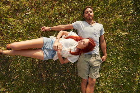 man lying down: Young man and woman lying on the lawn sleeping. Overhead view of young couple resting together on the grass. Stock Photo