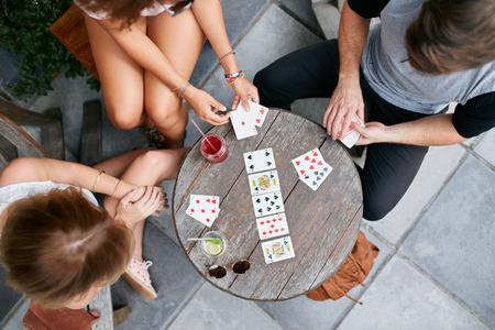 jugar: Vista superior de tres jóvenes jugando a las cartas en el café de la acera. Los jóvenes sentados alrededor de una mesa de café y jugando juego de cartas.