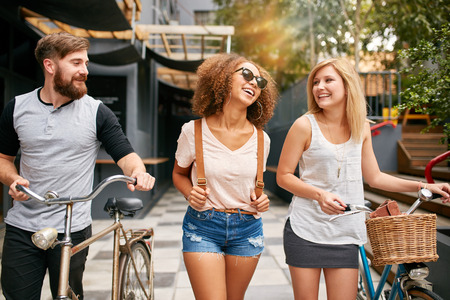 three day beard: Happy young people walking down the city street with their bicycles and smiling. Young man and women on road with their bikes. Stock Photo