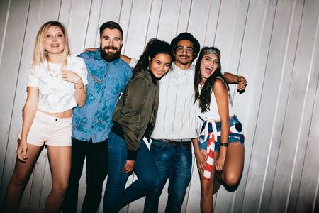 personas festejando: Felices los jóvenes de pie junto al aire libre y mirando a la cámara riendo. jóvenes amigos que cuelgan hacia fuera en la noche durante una fiesta.