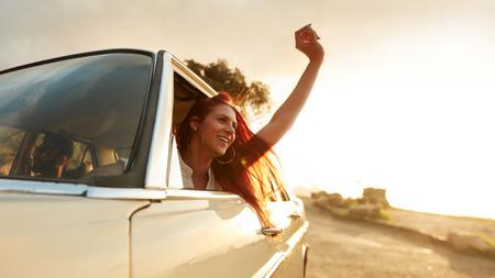 manos levantadas: Disparo de mujer que disfruta de viaje hermoso joven carretera en un día de verano. femenino joven emocionado que levanta su mano fuera del coche. Foto de archivo