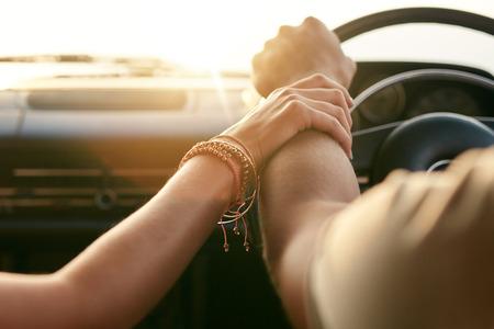 愛するカップルが車で旅行と手を繋いでのショットを閉じる。道路の旅行の男女の手に焦点を当てます。
