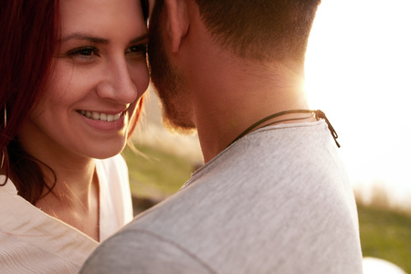 parejas romanticas: Close up shot of happy young woman embracing her boyfriend and looking away smiling. Loving young couple outdoors.