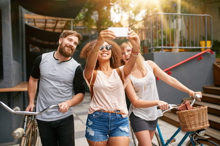 biker man: Young african woman taking a self portrait with her friends. African woman taking selfie with mobile phone. Young friends with bikes having fun on city street.