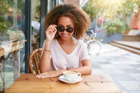 drink coffee: Portrait of pretty young girl at outdoor cafe.  African young woman wearing sunglasses looking at camera. Stock Photo