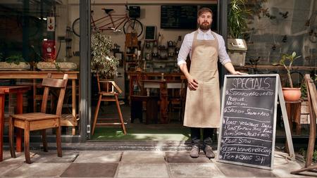 블랙 보드와 함께 자신의 커피 숍의 입구에 서있는 젊은 남자의 초상화. 바리 스타는 레스토랑의 출입구에 서.