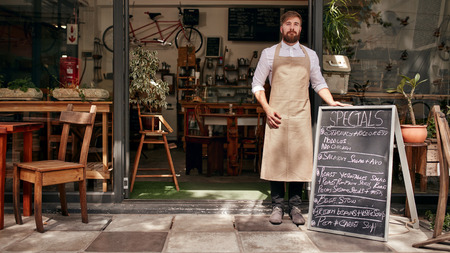 meseros: Retrato de hombre joven de pie en la entrada de su tienda de caf� con un tablero negro. Barista pie en la puerta de un restaurante.