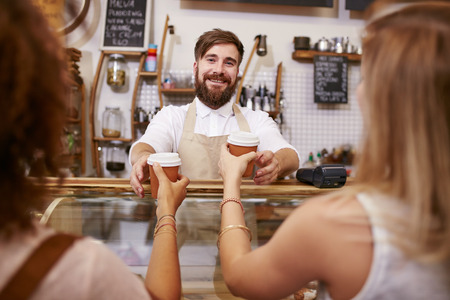 food store: Friendly young man with beard standing behind the cafe counter and serving coffee for two women. Young man working in restaurant, helping customer with coffee.