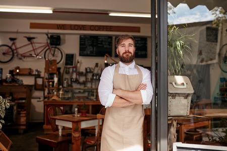 Schot van cafe eigenaar zich trots in de deuropening van zijn restaurant. Jonge man met een schort stond met zijn armen gekruist op de deur van een café.