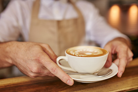 servings: Close up of man serving coffee at cafe. Focus on male hands placing a cup of coffee on wooden counter.