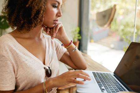 usando computadora: Cierre de tiro de joven mujer africana que trabaja en la tienda de café. Adolescente que usa la computadora portátil en la cara. Foto de archivo