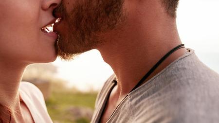屋外キス愛情の若いカップルのショットを閉じる。若い男と女の愛のトリミング。