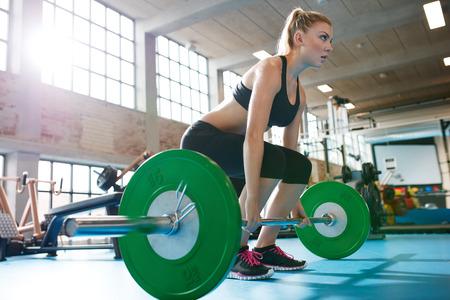 Mujer caucásica muscular en un gimnasio haciendo ejercicios de peso pesado. Mujer joven que hace levantamiento de pesas en el gimnasio. Foto de archivo