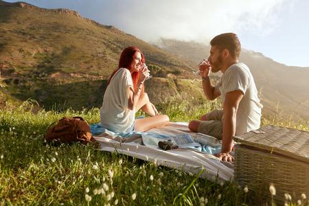 와인을 마시는 젊은 부부 야외 샷입니다. 편안한 남자와 여자의 시골에서 여름 휴가에.